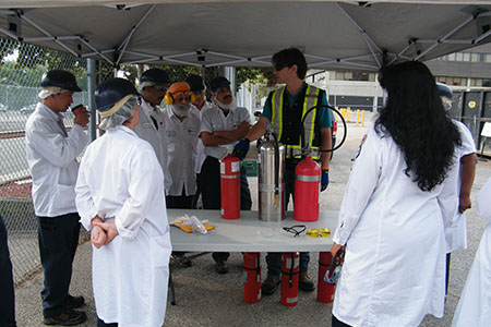 person teaching a workplace safety course outside with fire extinguishers